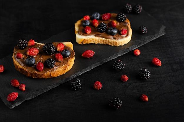 Тост с шоколадно-ореховым маслом со свежими лесными ягодами на темном фоне Premium Фотографии