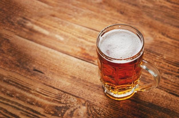 Полное стекло пива лагера на деревянной деревенской предпосылке. Premium Фотографии