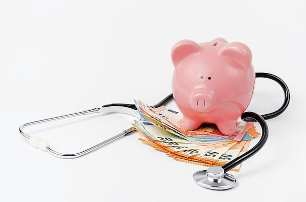 白い壁に聴診器、貯金箱、ユーロ通貨。コピースペース。医療保険の適用範囲の概念 Premium写真