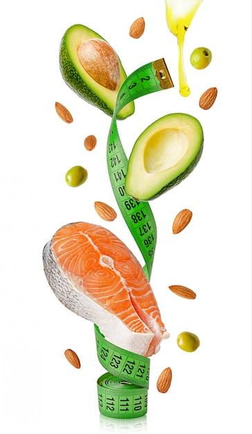 Лосось, авокадо, миндаль, оливки и масло, летающие вокруг измерительной ленты Premium Фотографии