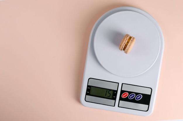 Сладкое миндальное печенье на кухонные весы на бежевом Premium Фотографии