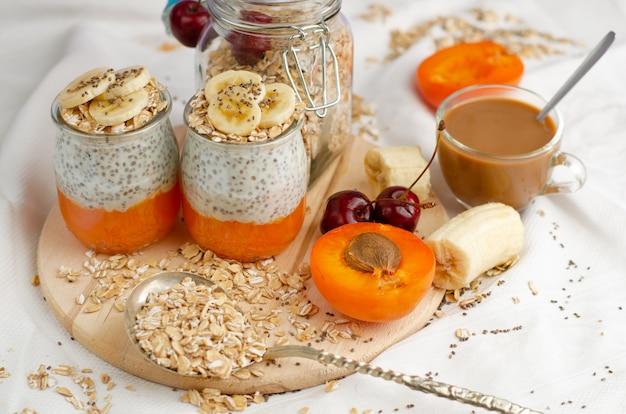 健康的なライフスタイルのコンセプトです。木の板にフルーツとコーヒー、エンバクの食事、チアシードプリンと朝食します。 Premium写真
