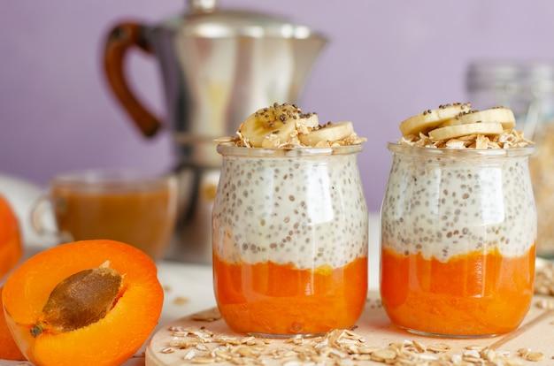 木の板にフルーツとコーヒー、エンバクの食事、チアシードプリンと朝食します。 Premium写真