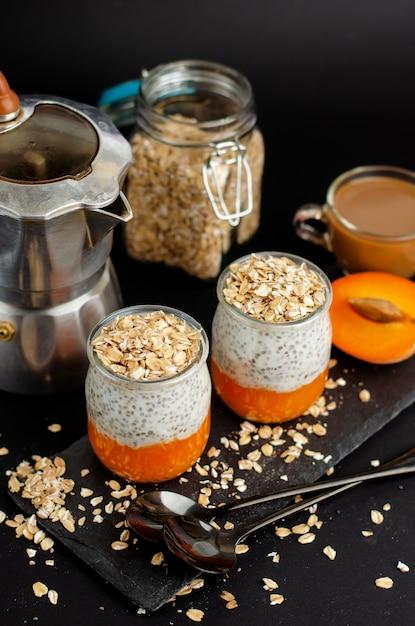 コーヒー、ヨーグルトチア、新鮮なアプリコットとオート麦フレーク添えブラックの朝食 Premium写真