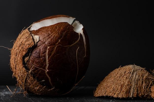 暗い背景に生の壊れたココナッツ。 Premium写真