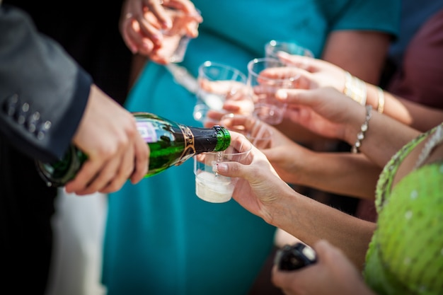 Мужчина наливает шампанское на бокалы. гости на свадьбе разливают шампанское. Premium Фотографии