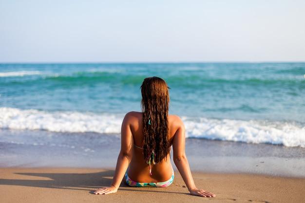 Силуэт молодой женщины на пляже. Premium Фотографии