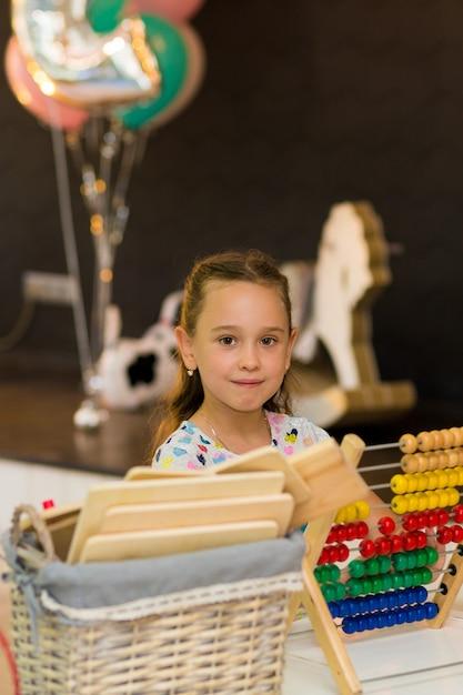 Смешная маленькая девочка держит большие красочные счета. Premium Фотографии