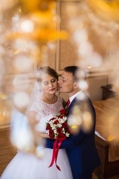 ホテルの部屋でキス、結婚式のブーケを持って新郎新婦 Premium写真