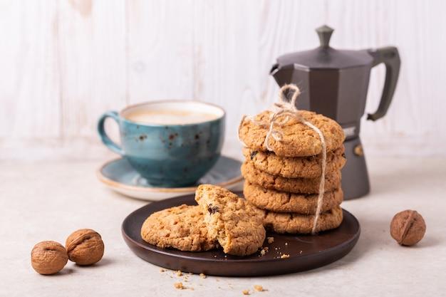 一杯のコーヒー、オートミールクッキー、白い木製の背景にコーヒーメーカー。 Premium写真