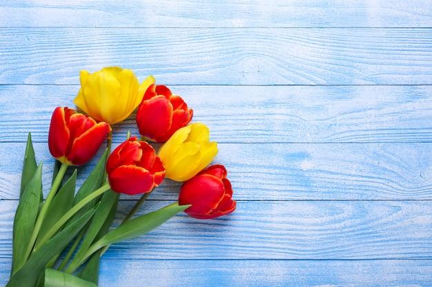 木製のテーブルに新鮮な色とりどりのチューリップの花の花束 Premium写真