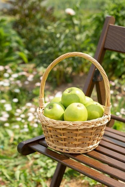 庭の椅子に籐のバスケットに青リンゴ Premium写真