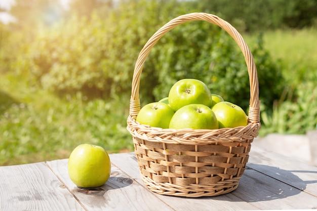 木製のテーブルの上の枝編み細工品バスケットの緑と赤のりんご庭の緑の芝生収穫時期太陽フレア Premium写真