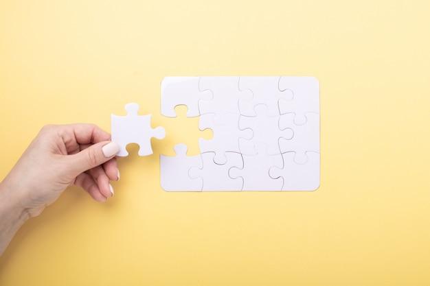 Последний кусок головоломки в руке белый пазл Premium Фотографии