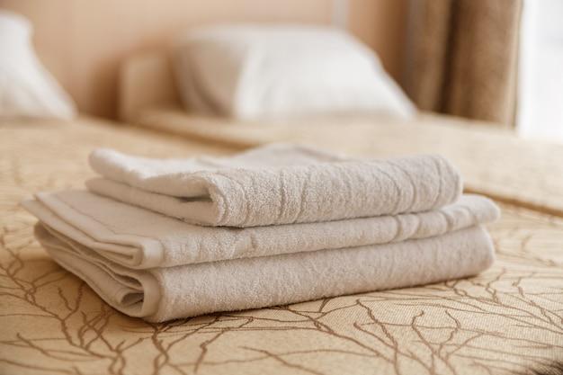 Стог белого полотенца гостиницы на кровати в интерьере спальни. Premium Фотографии