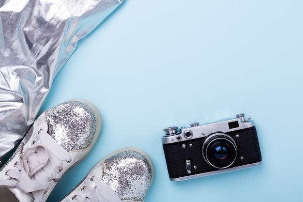 青色の背景にレトロなカメラでスタイリッシュな女性の春または秋の銀の靴 Premium写真