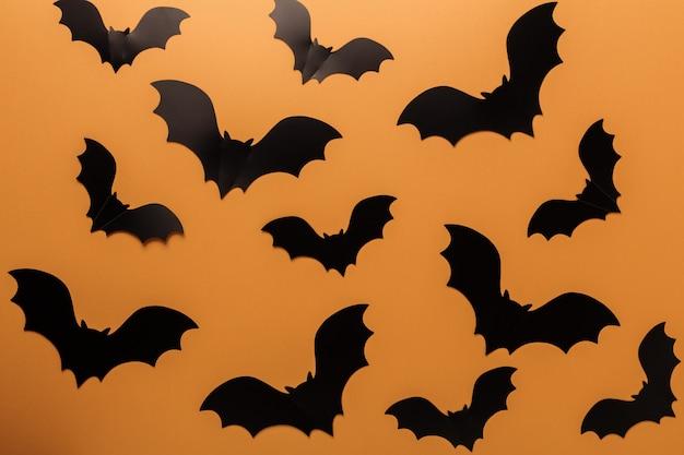 オレンジ色の背景にハロウィーン黒コウモリ Premium写真
