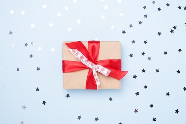 青の背景に紙吹雪星とクリスマスギフトボックス Premium写真