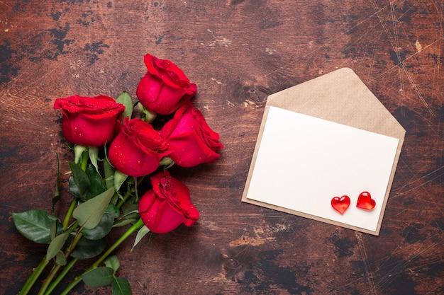 バレンタインのグリーティングカード赤いバラの花の花束とヴィンテージの木製の背景に赤いハートのクラフト封筒 Premium写真