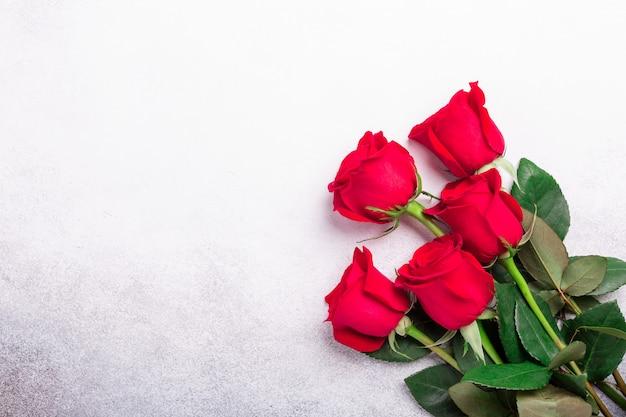 Красные розы цветы на фоне каменных. валентинка вид сверху. копировать пространство Premium Фотографии