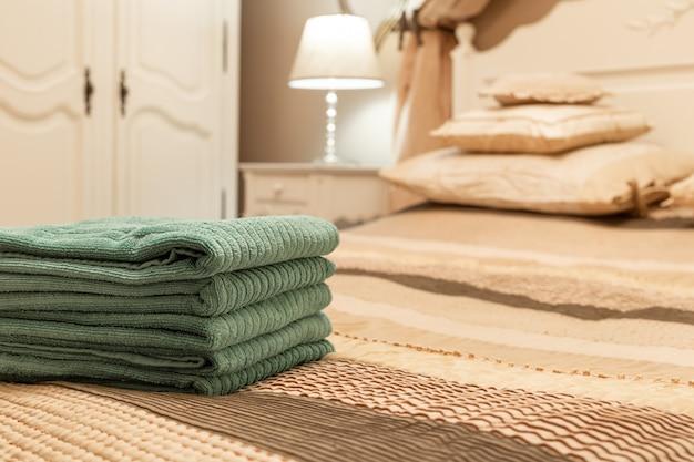 Стог зеленого гостиничного полотенца на кровати в интерьере спальни Premium Фотографии