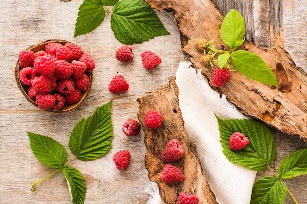 みすぼらしい木の上にボウル、ベリー、葉のラズベリー。上面図 Premium写真