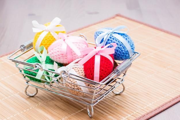 Вязаные пасхальные яйца перевязаны цветными лентами в металлической корзине на салфетке на столе Premium Фотографии