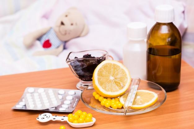 柔らかいおもちゃでテーブルの子供用ベッドに薬、ビタミン、レモン、ジャム Premium写真