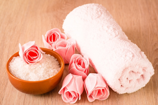 花、海の塩、木製の背景にタオルの形の石鹸 Premium写真