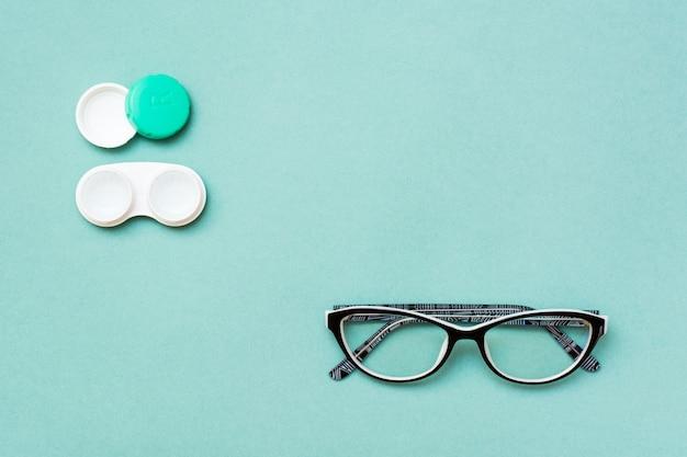 レンズとメガネの緑の背景を持つコンテナーを開く Premium写真