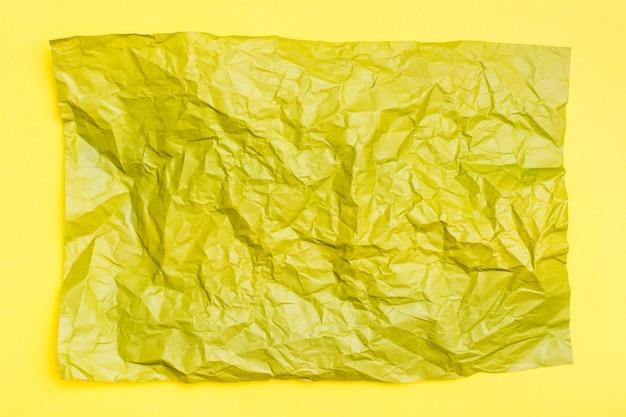 Прикройте скомканный желтый лист покрашенной бумаги на желтой предпосылке картона. текстурный разноцветный фон. вид сверху. копировать пространство Premium Фотографии