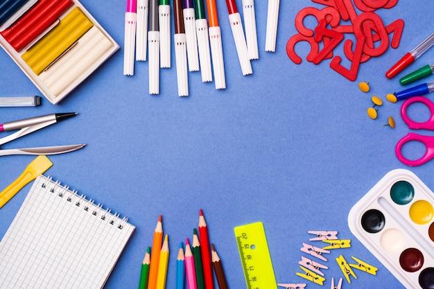 文房具、絵を描くためのオブジェクト、そして創造性が青の枠の中にレイアウト Premium写真