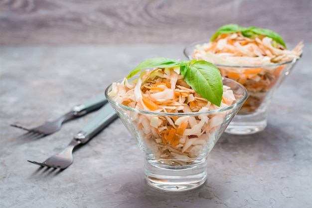Американский готовый к употреблению салат из капусты капусты, сельдерея, моркови и яблок с листьями базилика в стеклянных мисках на столе. Premium Фотографии
