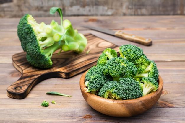 新鮮な生のブロッコリーを食べる準備ができて、木製のプレートとまな板と木製のテーブルにナイフで花序に分かれています。 Premium写真
