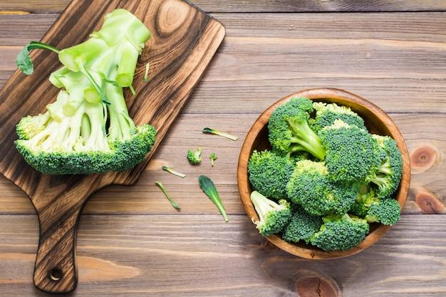 新鮮な生のブロッコリーを食べる準備ができては、木製のプレートと木製のテーブルのまな板の上の花序に分かれています。 Premium写真