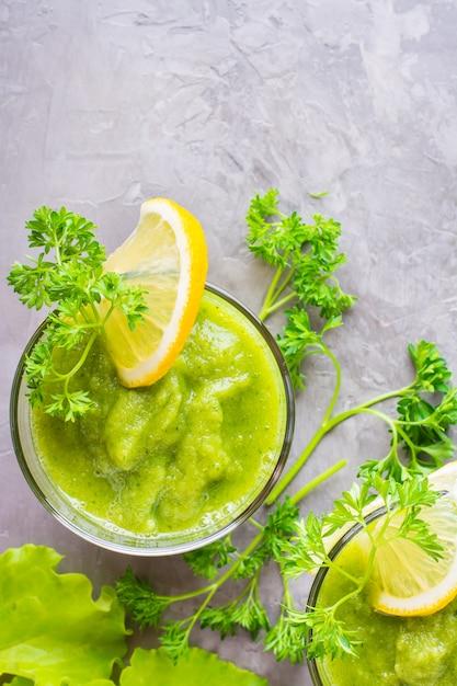 Освежающие смузи из огурца, зеленого яблока, зелени и лимонного сока в прозрачных стаканах на столе. концепция здорового питания. вегетарианское меню. вид сверху Premium Фотографии