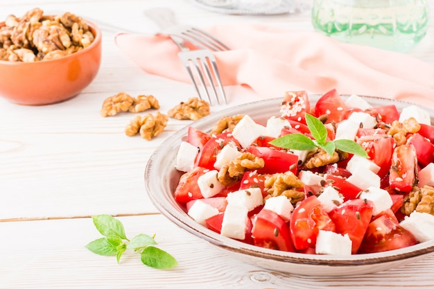木製のテーブルのプレートにトマト、フェタチーズ、クルミ、亜麻の種子、ゴマの新鮮な前菜 Premium写真
