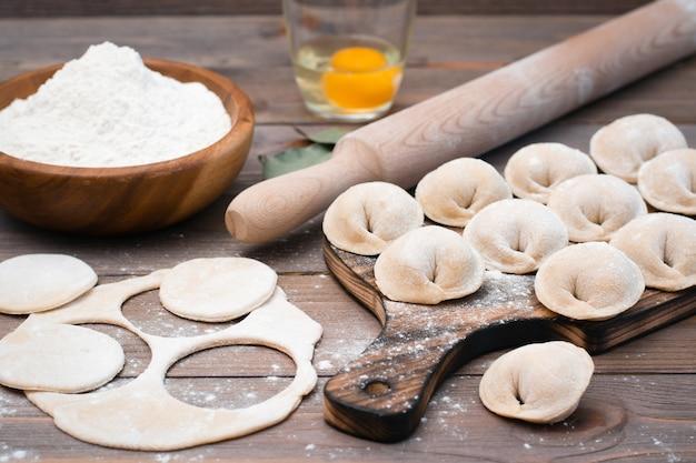餃子や木製のテーブルで調理するための食材を成形するプロセス Premium写真