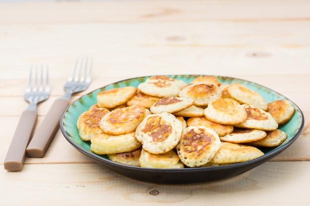 Тренд завтрак. голландские мини-блины на тарелку и две вилки на деревянном столе. Premium Фотографии
