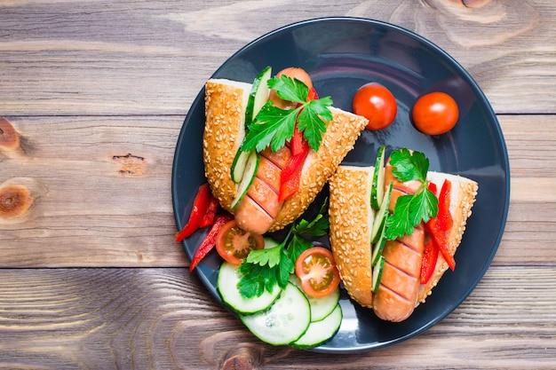 木製テーブルの上の皿に揚げたソーセージ、ごまパン、新鮮な野菜から出来上がったホットドッグ。上面図 Premium写真
