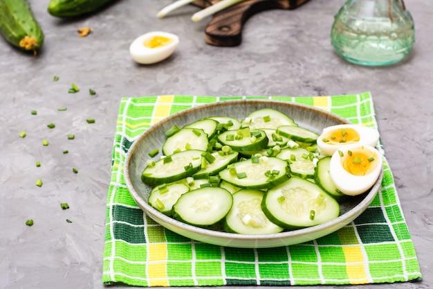 テーブルの上の皿に新鮮なキュウリのサラダ、ゆで鶏の卵、ねぎ Premium写真