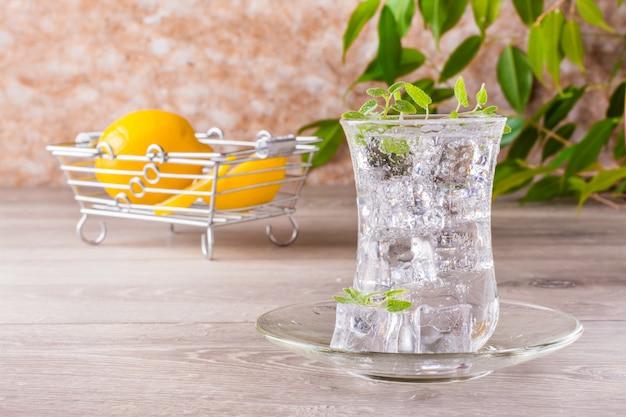 グラスに氷とミントの葉が入った爽やかなミネラルウォーター Premium写真