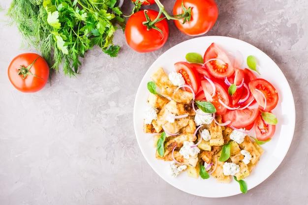 揚げズッキーニ、フェタチーズ、トマト、ハーブ、玉ねぎのプレート Premium写真