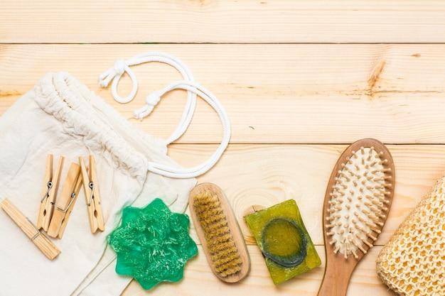 廃棄物ゼロのバスルームアクセサリー、天然サイザルブラシ、木製櫛、固体石鹸、キャンバスバッグ、天然木製の背景に木製洗濯はさみ Premium写真