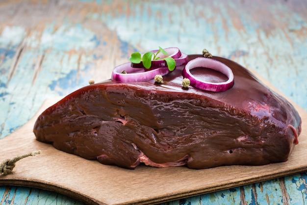 木製のテーブルで調理するための食材をボウルに生の牛レバーの部分 Premium写真