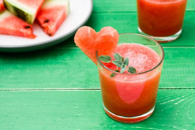 Свежий арбуз купажированный напиток с листьями мяты и сердцем арбуза в очках и ломтиками арбуза на деревянном столе Premium Фотографии