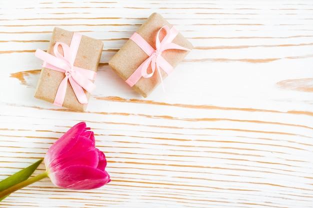 ピンクのリボンと白い木、上面にチューリップで包まれた贈り物のカップル Premium写真