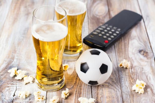 ビールと木製のテーブルの上の軽食 Premium写真