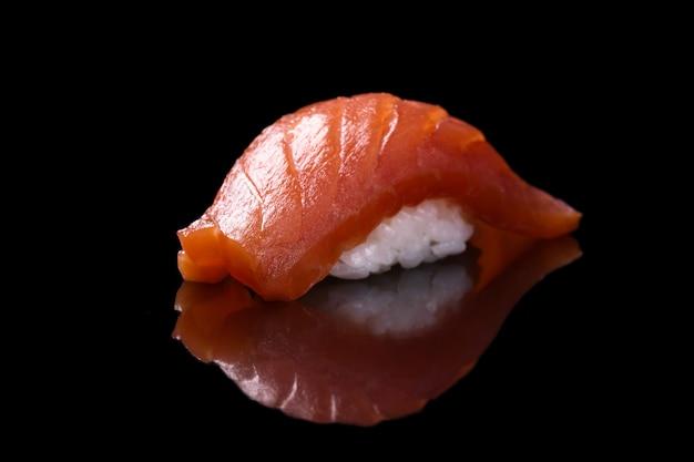 黒の上の寿司サーモン Premium写真