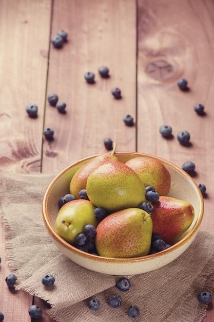 木製の背景に新鮮なブルーベリーとセラミックボウルのジューシーな梨 Premium写真